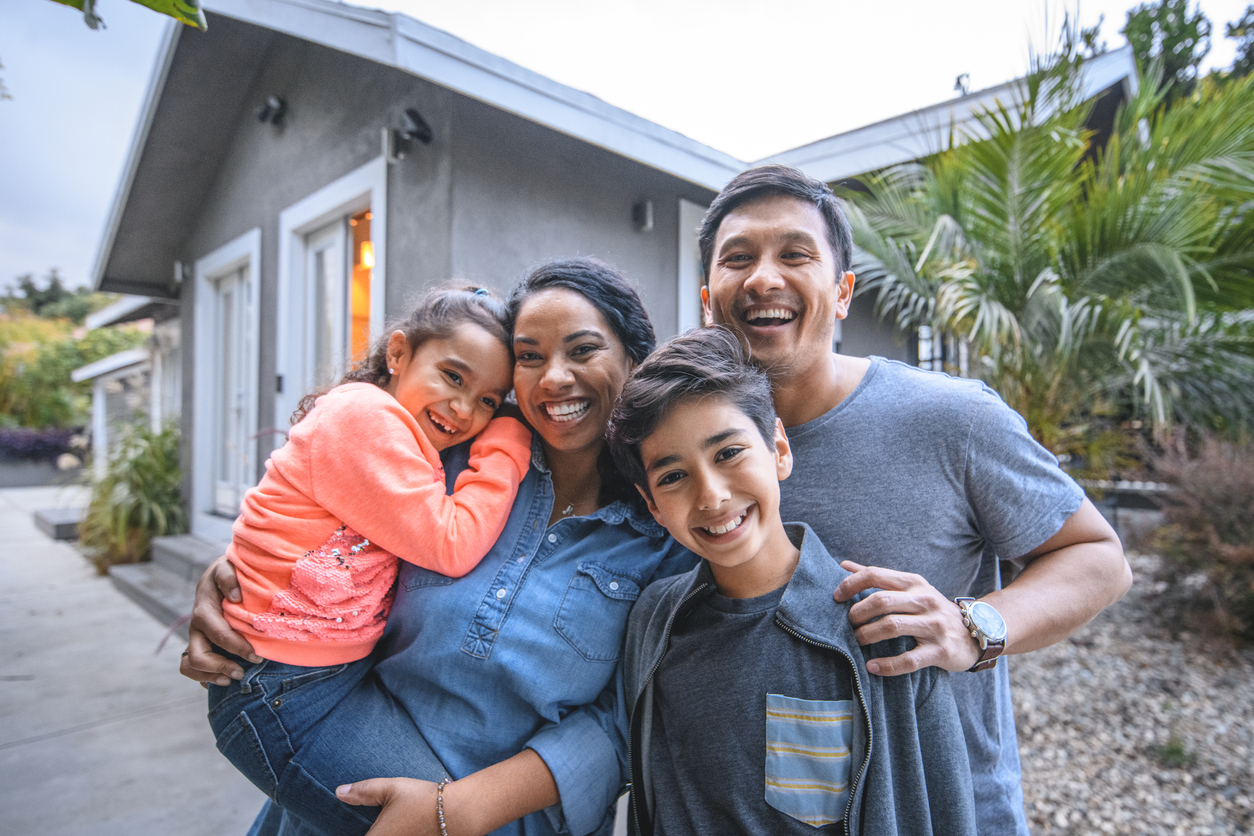 Portrait of happy family against house